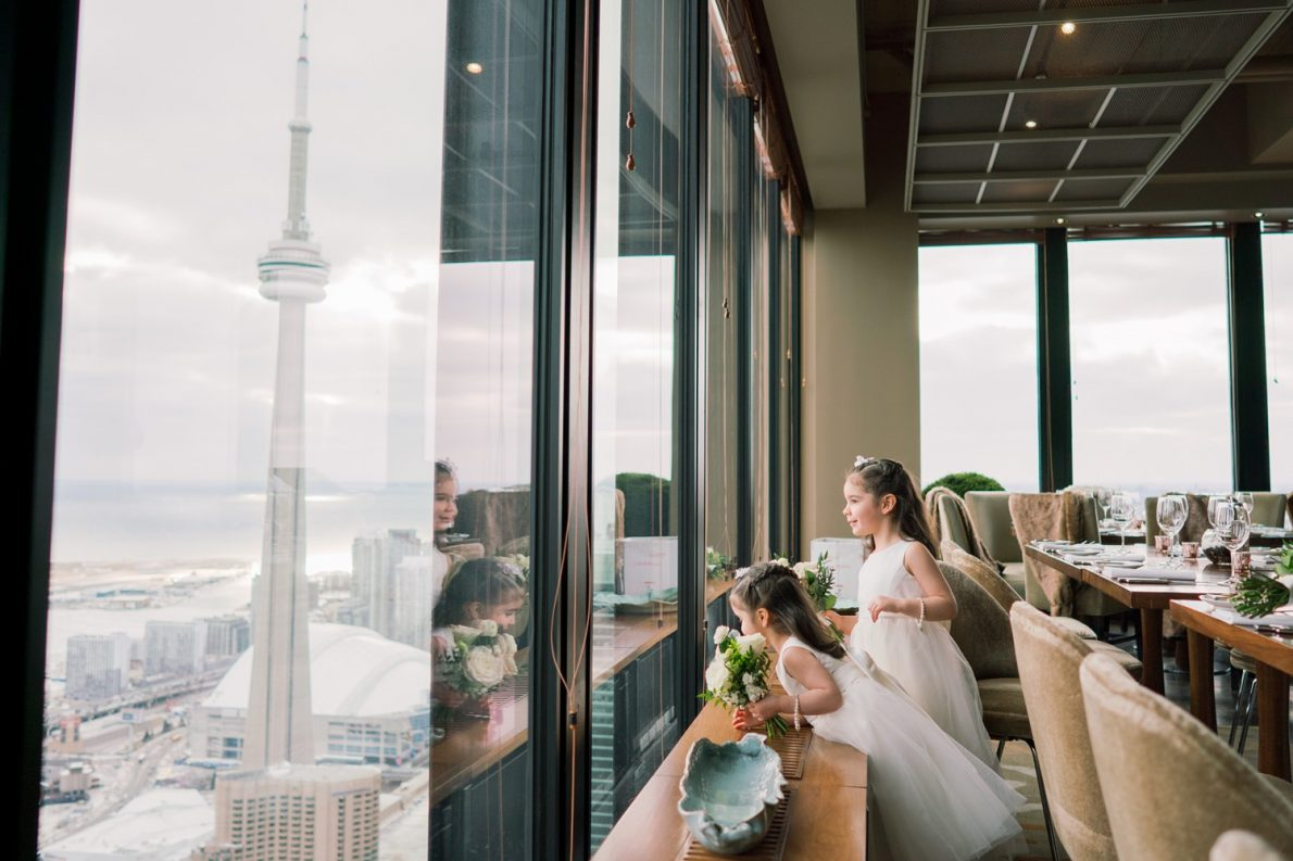 Flower Girls watching CN Tower Downtown Financial District Winter Canoe Restaurant Toronto Wedding Photos-Rhythm_Photography